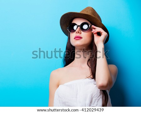 portrait of the beautiful young woman on the blue background - stock photo