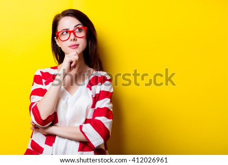 portrait of the beautiful young woman on the yellow background - stock photo