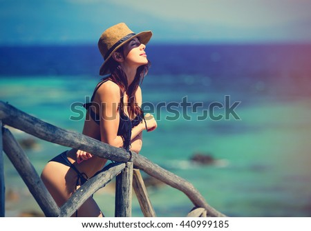 portrait of the beautiful young woman standing near the wooden railing resting in Greece