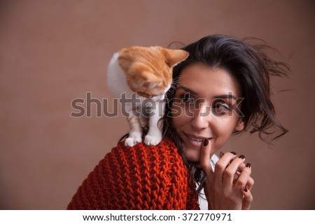 Portrait of the beautiful young woman with a kitten on the shoulder. Concept of loving animals, taking care and having fun with pets - stock photo