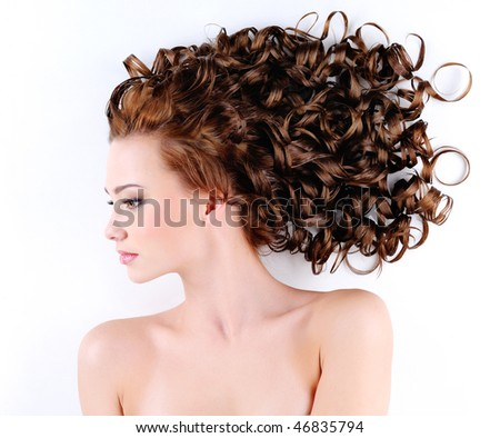 portrait of the beautiful young woman with beauty long ringlets hairs lying on the floor - stock photo