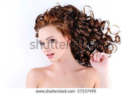 portrait of the beautiful young woman with beauty long ringlets hairs lying on the floor