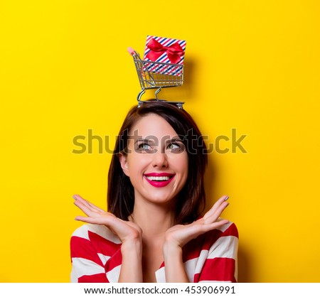 portrait of the beautiful young woman with cart and gift over head on the yellow background - stock photo