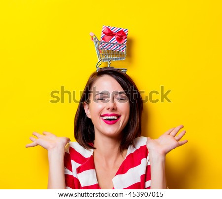portrait of the beautiful young woman with cart and gift over head on the yellow background