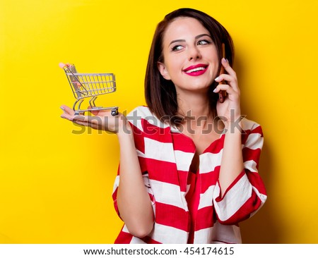 portrait of the beautiful young woman with cart for shopping and mobile phone on the yellow background - stock photo