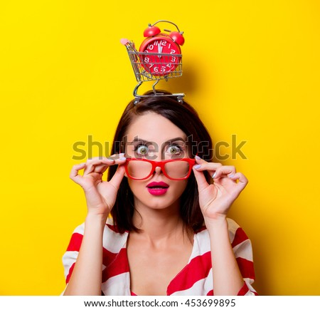 portrait of the beautiful young woman with cart for shopping and red alarm clock on the head on the yellow background - stock photo