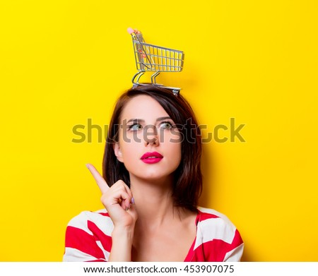 portrait of the beautiful young woman with cart for shopping on the yellow background - stock photo