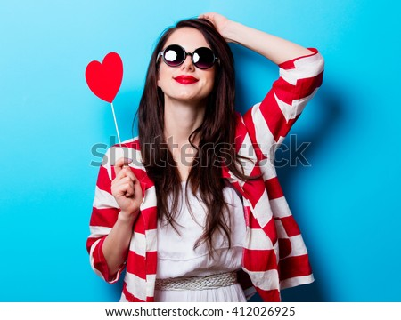 portrait of the beautiful young woman  with heart shaped toy on the blue background - stock photo