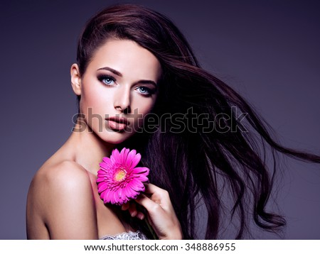 Portrait of the beautiful  young woman with long brown  hair with pink flower posing at studio over dark background