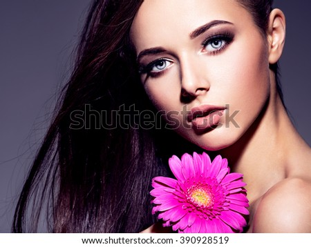 Portrait of the beautiful  young woman with long brown  hair with pink flower posing at studio over dark background - stock photo