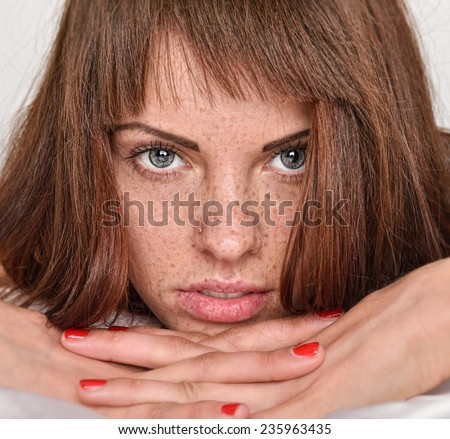 Portrait of the beautiful young woman with red hair and freckles. She is lying in the bed - stock photo