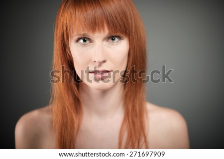 Portrait of the beautiful young woman with red long hair on dark background