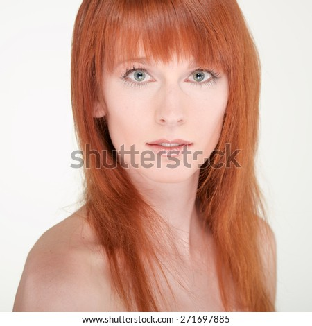 Portrait of the beautiful young woman with red long hair on white background