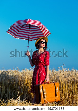 portrait of the beautiful young woman with red umbrella and brown suitcase standing in the field - stock photo