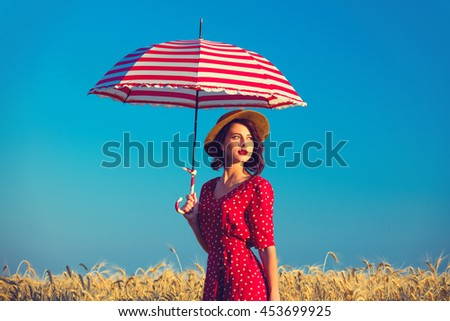 portrait of the beautiful young woman with red umbrella standing in the field