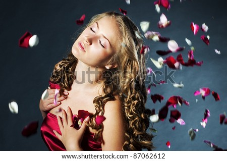 Portrait of the beautiful young woman with rose flower petals