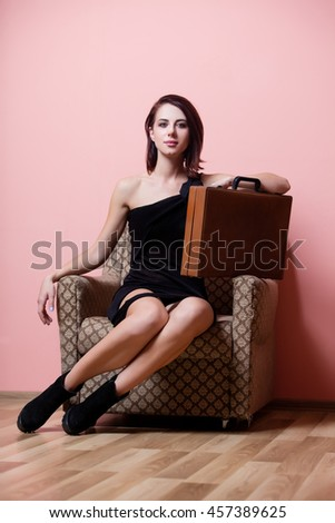 portrait of the beautiful young woman with suitcase in the armchair on the pink background