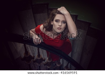 portrait of the beauty woman wearing red dress sitting on the stairs - stock photo