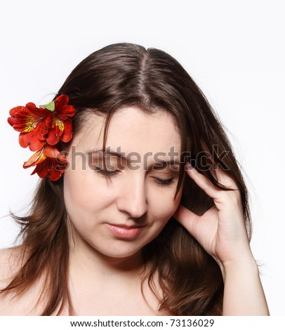 Portrait of the beauty young brunette girl with lily in her hair - stock photo