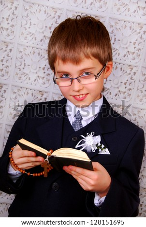 portrait of the boy going to the first holy communion  with prayer book and rosary - stock photo