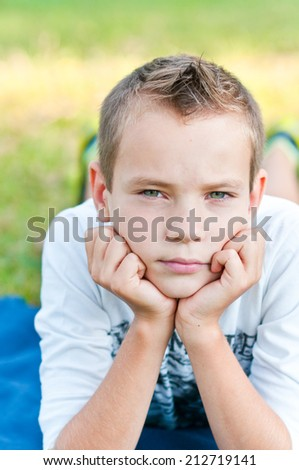 Portrait of the boy in park on a grass - stock photo