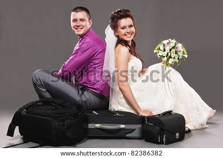 Portrait of the bride and the groom in studio on a grey background