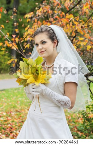 Portrait of the bride on a background of autumn leaves - stock photo
