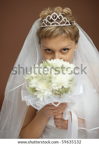 Portrait of the bride with a bunch of flowers at the face on a brown background - stock photo