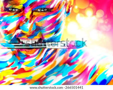 Portrait of the bright beautiful emotional woman with art make-up and brush in her mouth - stock photo