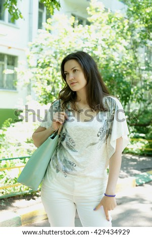 Portrait of the brunette in the summer outdoors
