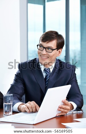 Portrait of the businessman with the laptop at office - stock photo