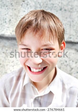 Portrait of the Cheerful Kid on the Wall Background outdoor - stock photo