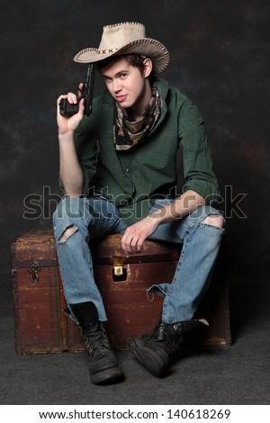 Portrait of the cowboy   sitting on an old trunk with pistols - stock photo