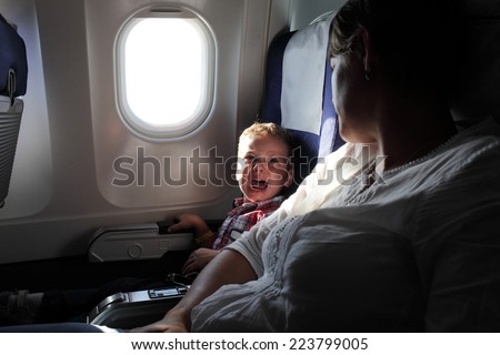 Portrait of the crying boy on the flight - stock photo