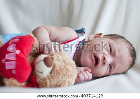 Portrait of the crying Little baby with toy bear - stock photo