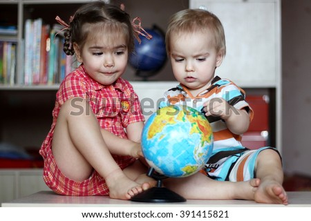 Portrait of the cute girl with her little brother looking at the earth globe, save the earth concept