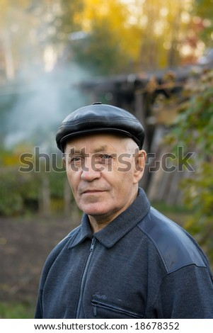 Portrait of the elderly man in a cap against the nature