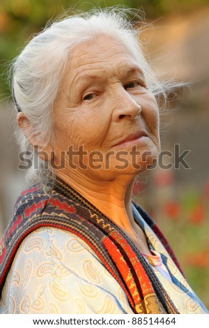Portrait of the elderly woman. A photo on outdoors - stock photo