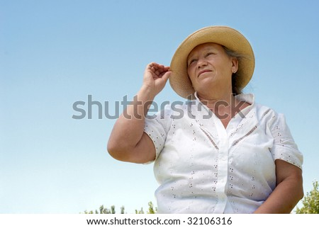 Portrait of the elderly woman against the sky - stock photo