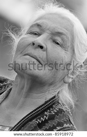 Portrait of the elderly woman. Monochrome. A photo on outdoors - stock photo