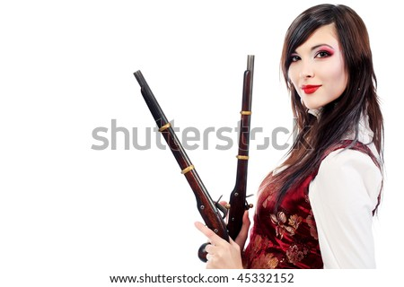 Portrait of the elegant young woman in 19th century costume holding guns in her hands. Shot in a studio.