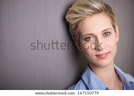 Portrait of the face of a beautiful modern young woman with a short blond hairstyle on a grey background with copyspace - stock photo