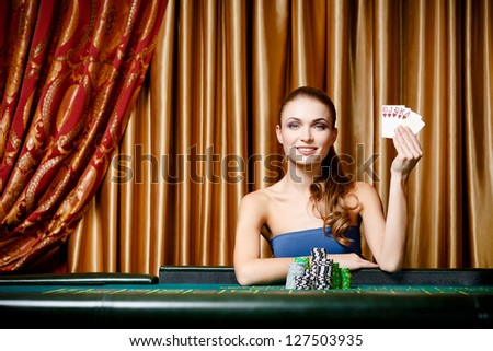 Portrait of the female gambler at the poker table handing cards - stock photo