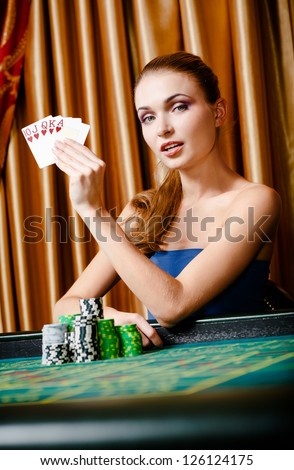 Portrait of the female gambler with cards and chips at the poker table - stock photo