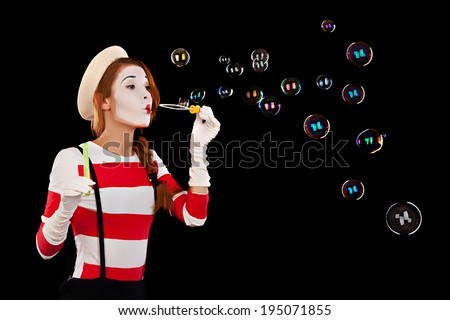 Portrait of the female MIM comedian blows soap balls, isolated on black background. - stock photo