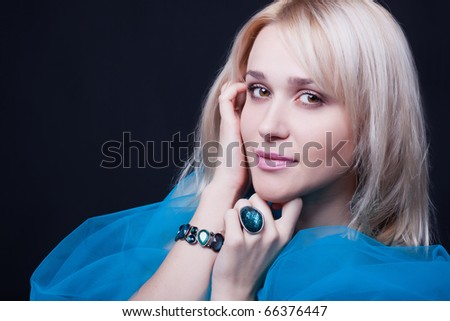Portrait of the fine young woman with a bright scarf ?nd accessories On a black background