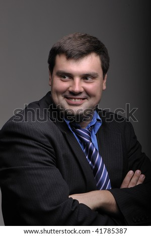 Portrait of the full smiling young businessman on a dark background