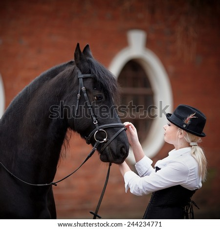Portrait of the girl and black horse. The girl communicates with a beautiful horse. Equestrian sport. - stock photo