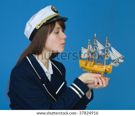 Portrait of the girl blowing on sails of the ship - stock photo