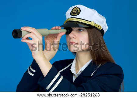Portrait of the girl - captain with telescope on a blue background